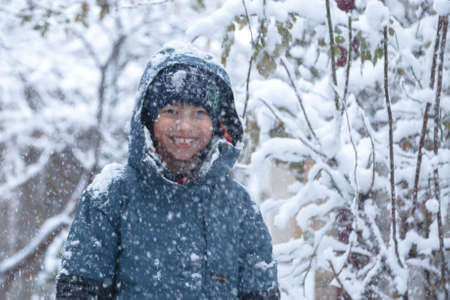 Outdoor winter portrait of little healthy happy baby child walking in the park on cold day with snow and snowfall. Stylish clothes for kids.