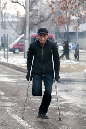 Bishkek-Kyrgyzstan. January 2021. A crippled beggar on the road asks for help. Poverty