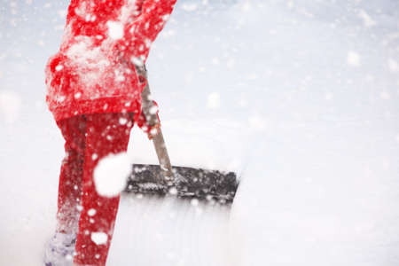 Outdoor winter portrait of a small healthy happy child with a shovel in hand, snow removal 免版税图像
