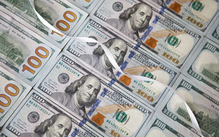white gift ribbon on top of American dollars. money background.