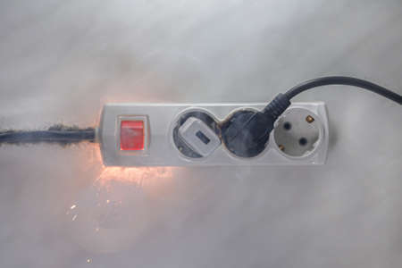 Inflamed plug in power board - result of electrical short circuit, selective focus
