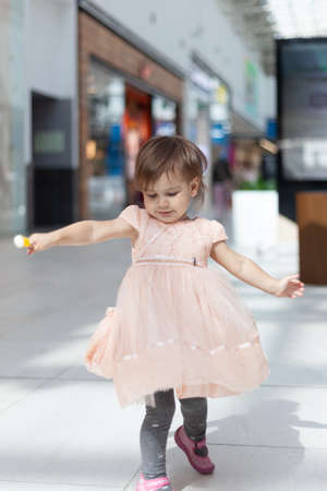 Baby in a dress smiles, on the background of a shopping center