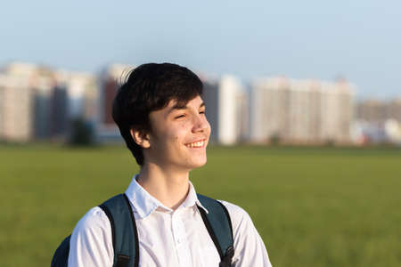 Portrait of a happy smiling teenager with a backpack, a school teenager waiting for a school bus, on his way to school. On the way home from school against the background of the urban landscape
