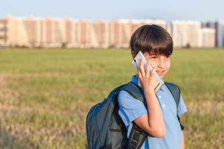 Schoolboy with backpack in his hands mobile phone against the background of the city landscape. Standard-Bild