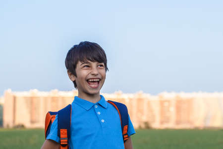 Portrait of happy boy with backpack, school child waiting for school bus, primary school student, on the way to school