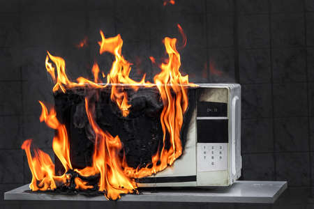 Microwave oven white, in fire front view, electrical appliances caught fire as a result of improper operation