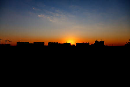 Silhouettes of buildings at sunset or sunrise, the architecture of modern construction.