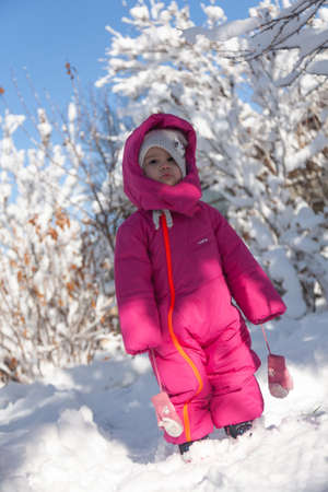 Outdoor winter portrait of little healthy happy baby child walking in the park on cold day with snow and snowfall. Selective focus