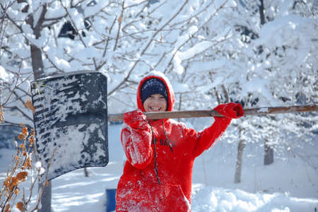 Outdoor winter portrait of a small healthy happy child with a shovel in hand. Standard-Bild