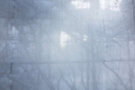 water drops on the fogged glass in the house against the background of winter Standard-Bild