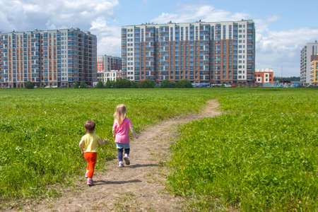 Children on the grass in front of the new neighborhood