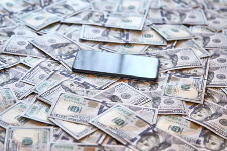 mobile phone on the background of money, the concept of profit