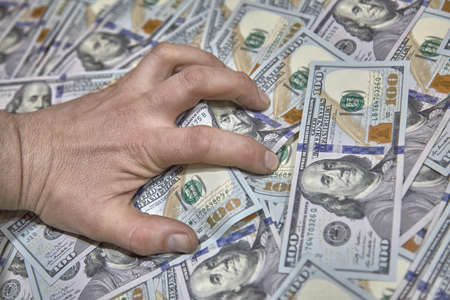 hand clutching money, the concept of greed