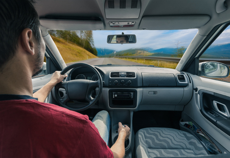 車と空のアスファルトの道路にステアリング ホイール上のドライバーの手