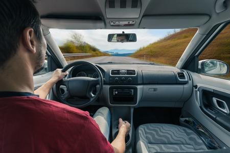 Man handen van een chauffeur op het stuur van een minivan auto op asfalt weg