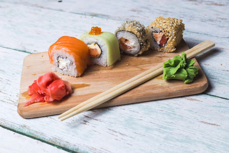 tekka: Sushi rolls on a wooden board with soy sauce, wasabi and pickled ginger on white vintage background Stock Photo