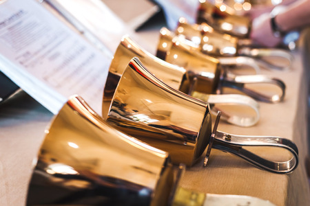 Golden handbells on table with sheet of notes Фото со стока - 53832700
