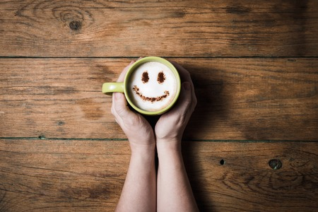 Cappuccino coffee with smiley face on wooden table in female hands overhead view Stock Photo