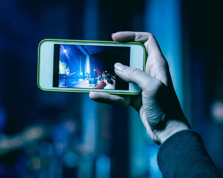echnology: Girl holding smart phone in hand and photographing concert Stock Photo