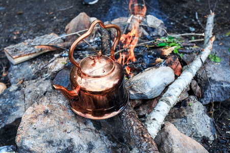 Metal camp kettle hanging over the coals campfire