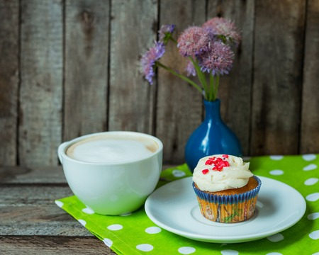 Cappuccino and cupcake on vintage wooden background with flower