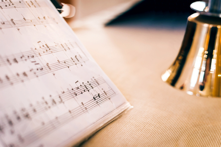 Handbells met blad van muziek op de tafel Stockfoto - 65067780