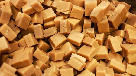 Caramel candies as background. Golden Butterscotch toffee caramels. Toffees.