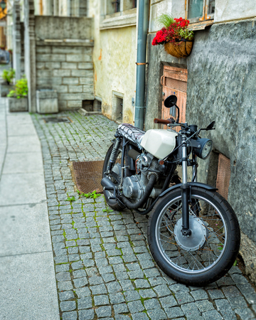 rebuilt: Silver rebuilt motorcycle cafe-racer parked by the wall in the empty street. Wild lifestyle