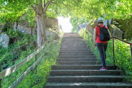 Young hiking woman in hat with backpack climbing the stone stairs to peak