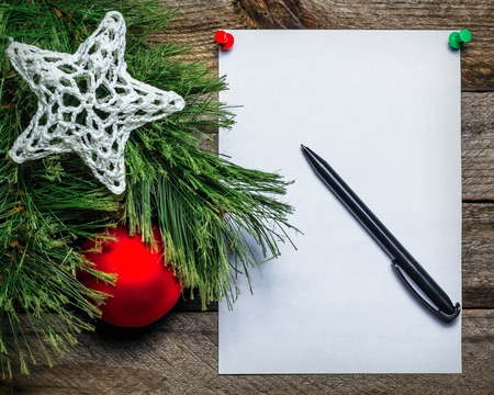 red christmas ball: Christmas background with red Christmas ball and paper with pen for your text. Vintage gray wall