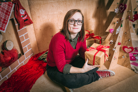 christmas budget: Christmas Girl Holding Presents in Gift Shop - Beautiful smiling woman holding a pile of wrapped Christmas gifts Stock Photo