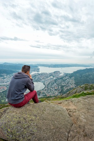 Young man in sportswear is sitting on cliffs edge and looking to misty valley bellow, Bergen, Norway Stock Photo
