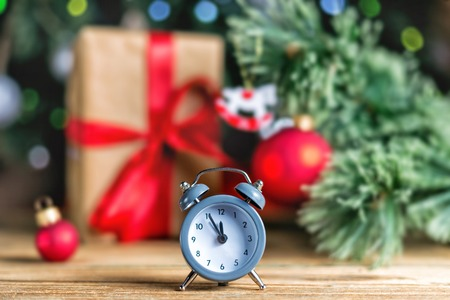 Christmas decoration red ball, baubles and antique clock on wooden background