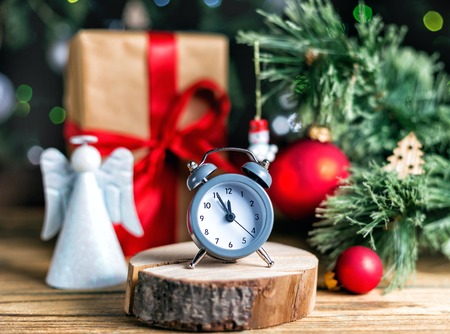 Christmas decoration red ball, baubles, angel and antique clock on wooden background Stock Photo