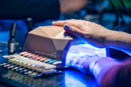 Manicurist putting shellac on the fingernails of a lady client in a beauty salon with a small applicator. Master with beautiful shellac manicure.