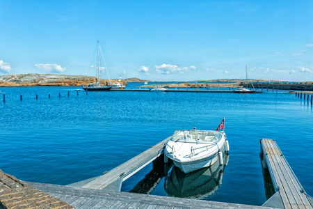 ende: One white boat in a small harbor. Bay of Verdens Ende in Norway