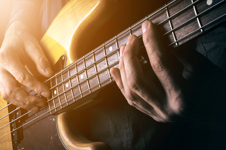 Live rock music background, electric bass guitar over bright blurred stage lights, close up Stock Photo