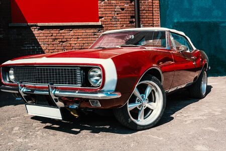 hot red muscle car on brick wall background