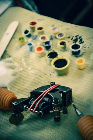 tattoo machine on the desk and cups of ink