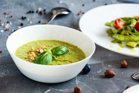 green cream soup, salad with asparagus and cherry tomatoes on the gray background