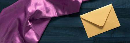envelope and pink textile on the dark wooden gray table horizontal, panorama,