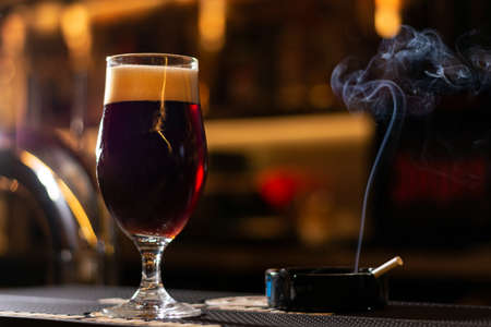 glass of dark craft cherry beer and cigarette on blurred background close up Banque d'images