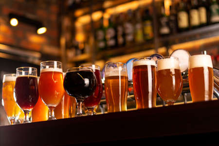 a lot of craft golden beer on bar table in worm lights and blurred background Banque d'images