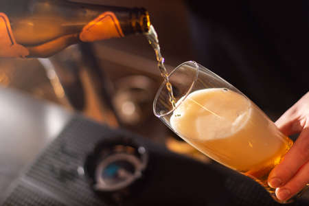 bartender pouring golden craft beer in to the glass on blurred background and warm lights behind Banque d'images