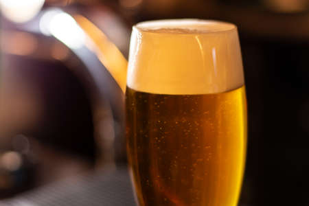 a glass of cold craft golden beer whit high foam closeup blurred background Banque d'images