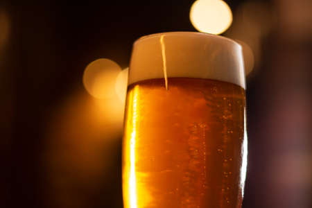 glass of golden craft beer with foam close up on blurred background