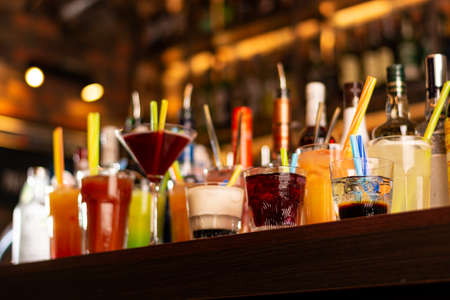 a lot of colorful drinks on bar table on blurred lighting background Banque d'images