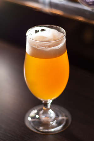 bright glass full of golden craft beer on bar table close up