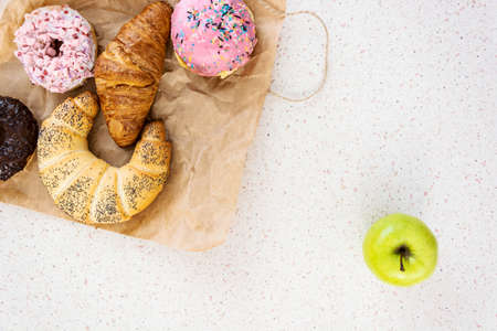 sweets or healthy food close up white table green apple fruit and baked sweets Banque d'images