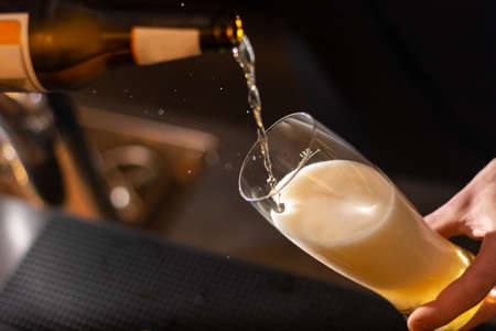 bartender pouring a golden craft beer to glass close up on blurred background